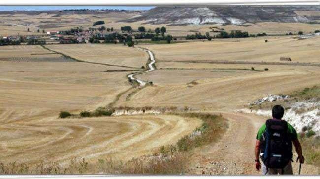 Hombre caminando en dirección a unla localidad despoblada de Palencia