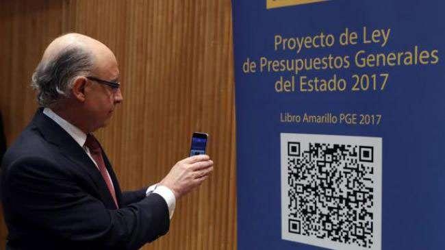El ministro de Hacienda Cristóbal Montoro frente a un cartel de los Presupuestos Generales del Estado